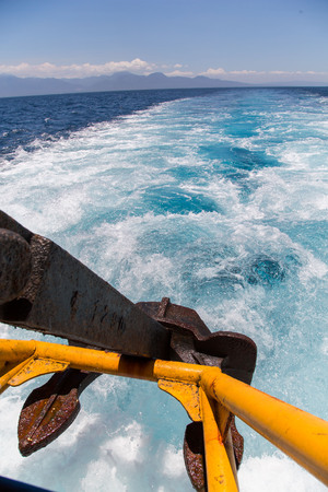 lifted anchor over Wake water of a ferry boat with white foam, blue sky and deep blue sea on a sunny summer day