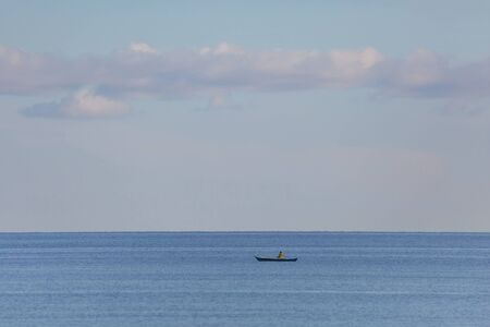 Fisherman in the blue sea with blue sky and white clouds and copy space a tranquil seascape scene