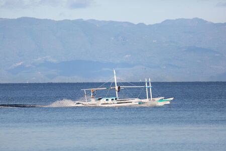Boat outrigger in high speed with dynamic backwash in front of an island coastline with green hills and mountain 版權商用圖片