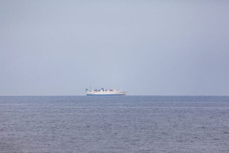 Ferry for passengers and cars in the blue sea with blue sky and white clouds and copy space a tranquil seascape scene