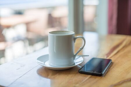Wooden table with cell phone, mobile phone and a mug of coffee in a relaxing break time scene 免版税图像