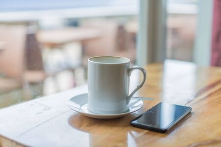 Wooden table with cell phone, mobile phone and a mug of coffee in a relaxing break time scene 版權商用圖片