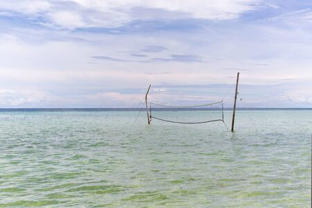 Beach volleyball net at the white beach in high tide flooded on a sunny summer day, no people relaxing vacation scene