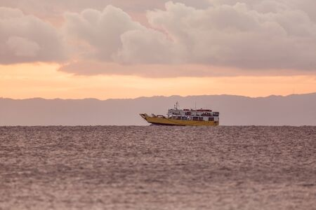 Ferry for passengers and cars in the open sea in sunset dusk and white clouds and copy space a tranquil seascape scene