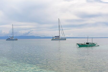 Catamaran sail boat at the coast line anchoring, in a luxury lifestyle summer sunny day photo