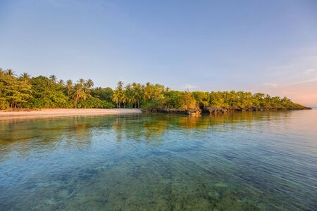 White sand beach with palm trees in sunset golden hour a summer sunny vacation image 版權商用圖片