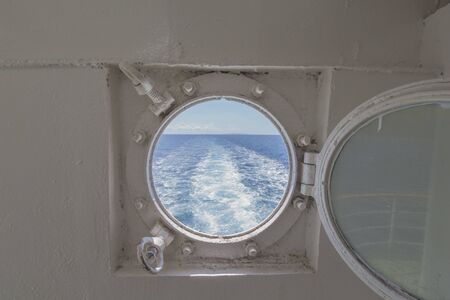 Metal porthole on a fast ferry with the view of the backwash and waterway