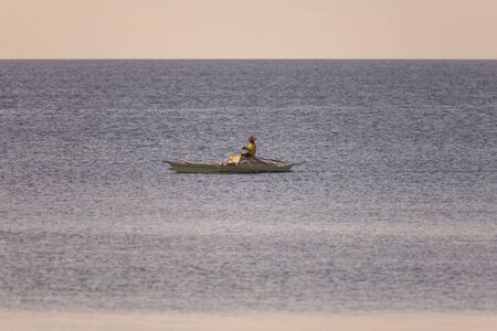 Fisherman in the blue sea. Successful fisherman with a copy space in a tranquil seascape scene