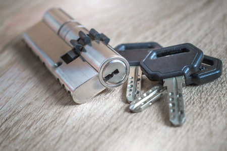 door lock with keys on wooden surface, close up