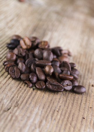 roasted coffee bean spilled on old plank Stock Photo