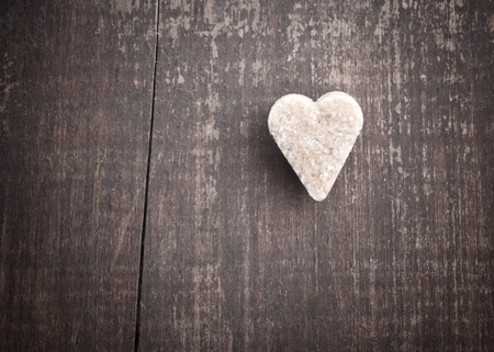 Heart-shaped sugar on old wooden table Stock Photo