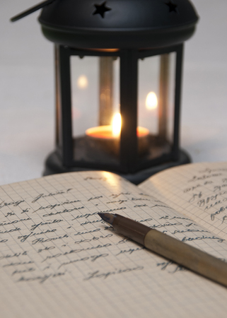 Antique black candlestick, candle and old letter, close up