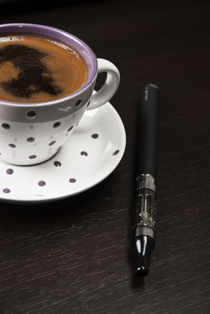 coffee cup and e-cigarette on table,close up photo