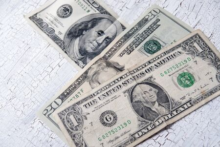 different dollar bills on wooden table, close up photo