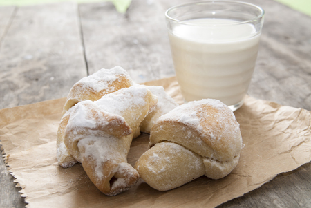 Milk and sweet rolls with sugar on a wooden background, close up photo