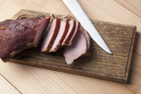 Smoked meat on wooden cutting board, close up