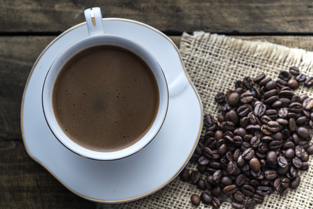 Cup of coffee and coffee beans, from above Stock Photo