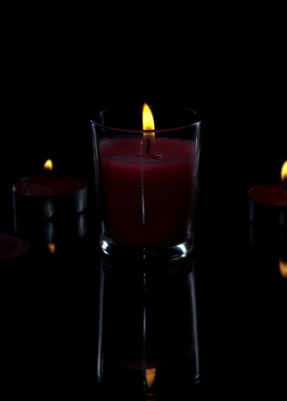 candle light with back light on a black background with reflection, close up 스톡 콘텐츠