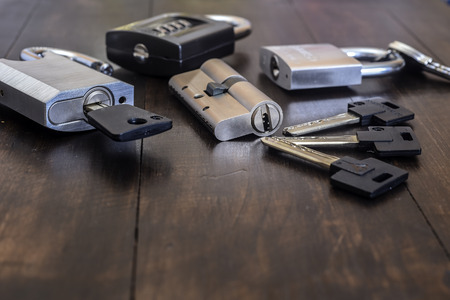 A new lock with keys on a wooden table. Close up Stock Photo