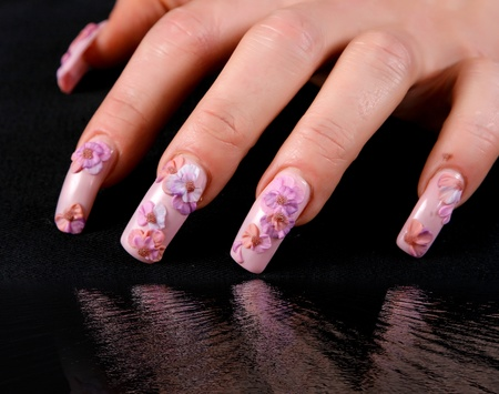 Beautiful woman hand with  manicure, over black background
