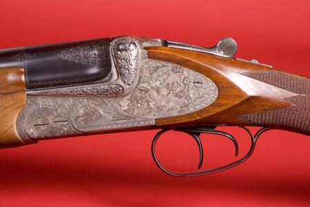 Detail of old shotgun on a red background