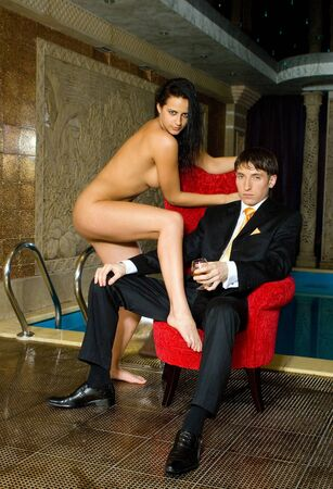 young guy in a suit against the naked girl pool