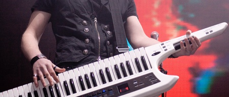 man playing on a synthesizer on a dark background
