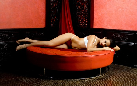Pretty girl on the red sofa. Beautiful woman. Stock Photo