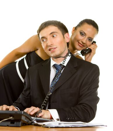 young businessman with telephone wire around his neck on a computer and a young business woman with a telephone receiver on white background photo