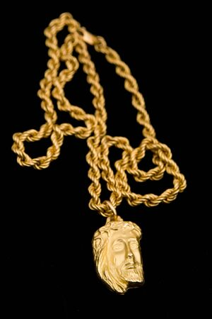 Gold pendant in shape the face of Christ in isolation on a black background
