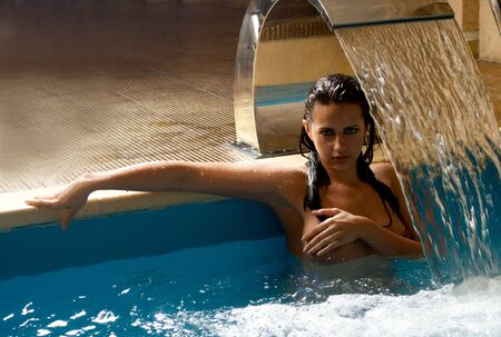Young sexy woman in a swimming pool photo