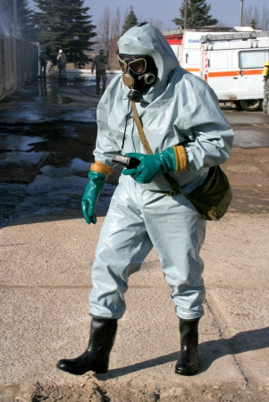 Man in chemical protection suit, carrying out the decontamination area photo