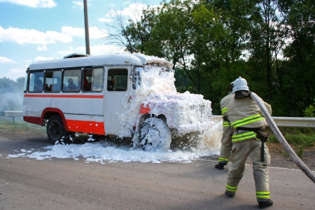 Firefighters extinguish a fire in a burning bus standing at the side of the road photo