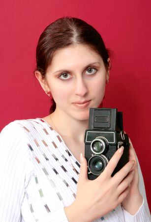 An excited young woman shouting holding a camera in hand against red background photo