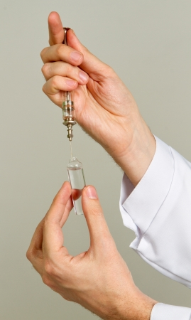 Left hand holding a syringe and vial close on a white background. Stock Photo - 17012854
