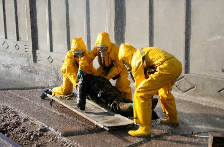 man in a yellow chemical protection suit running in the rain Stock Photo