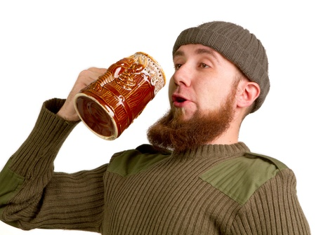 Happy young, bearded guy drinking beer from the glass on a white background