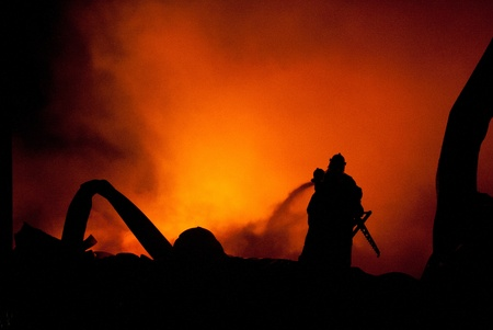 Silhouette of Firemen fighting a raging fire with huge flames of burning timber photo