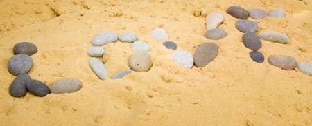 The inscription on the sand lined with sea stones - love. Background. photo