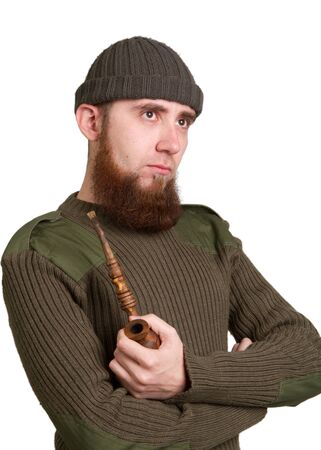 young bearded guy smoking a pipe on a light background photo