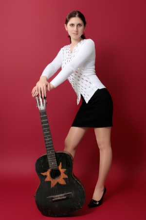 beautiful young brunette with a black guitar on a red background photo