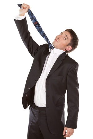 Caucasian mid-adult man pulling necktie out to choke himself while making facial expression  isolated on white background photo