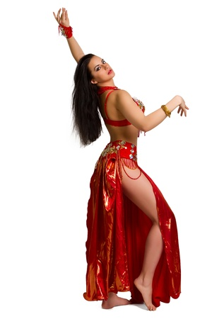 Beautiful young girl in a red suit oriental dance in motion isolated on white background photo