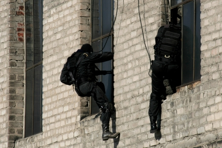 Subdivision anti-terrorist police during a black tactical exercises. Rope Techniques. Real situation.