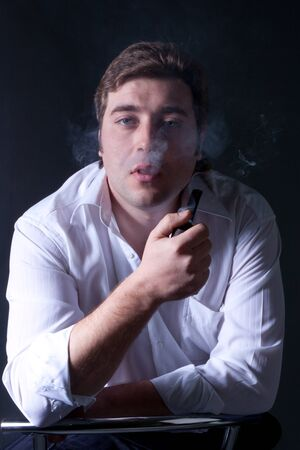 Artistic dark portrait of the young beautiful man smoking a pipe photo