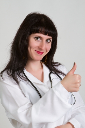 Happy smiling cheerful female doctor with thumbs up gesture, over grey background photo