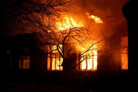 incendio casa: Antiguo edificio en el infierno llameante completo, y un bombero lucha contra las llamas Foto de archivo