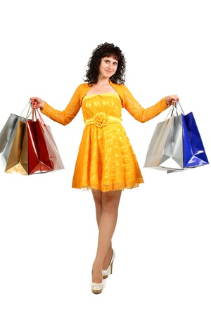beautiful young brunette in a yellow dress with shopping bags over white photo