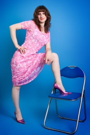 portrait of a beautiful young brunette in a pink dress on a  blue background photo