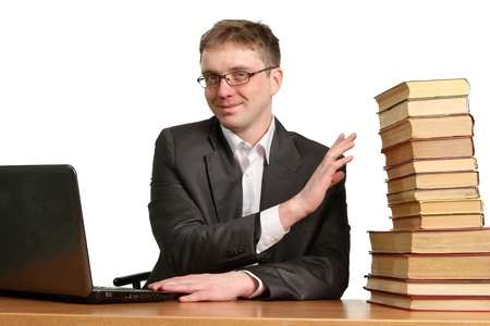 shrugs: young guy working at a laptop and shrugs off paper books isolated on white background